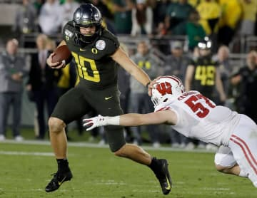Oregon quarterback Justin Herbert (10) stiff-arms Wisconsin linebacker Jack Sanborn on a 30-yard touchdown run in the fourth quarter during the Rose Bowl in Pasadena, Calif., on January 1, 2020. - Luis Sinco/Los Angeles Times/TNS