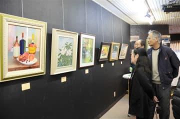 花や風景を描いた油絵などが並ぶ新春展=八代市