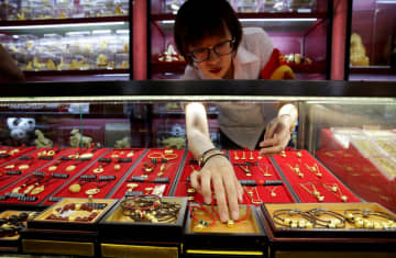 A sales assistant takes out gold ornaments for a customer at Caibai Jewelry store in Beijing.(Reuters photo)