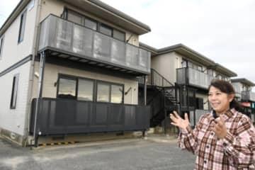再生予定のアパート前に立つ津田さん。災害時には部屋を避難場所として開放する計画だ
