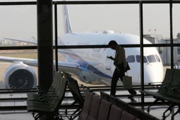 A passenger checks his phone at Phnom Penh's international airport. (Khmer Times photo)