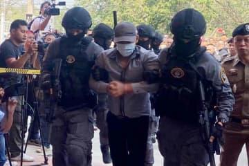Police commandos escort robbery-murderer suspect Prasitthichai Khaokaeo, 38, into the tourist police office in Lop Buri province on Wednesday. (Police photo)