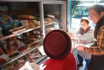 移動販売で地域を駆け回る山本さん(右)。買い物するお年寄りと世間話に花が咲く=南山城村高尾