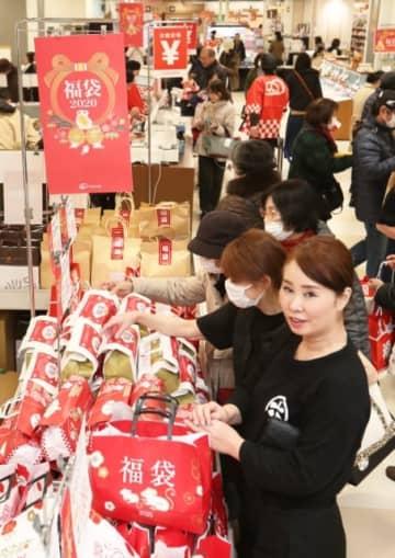店頭に並んだ福袋を選ぶ買い物客=1日、別府市のトキハ別府店