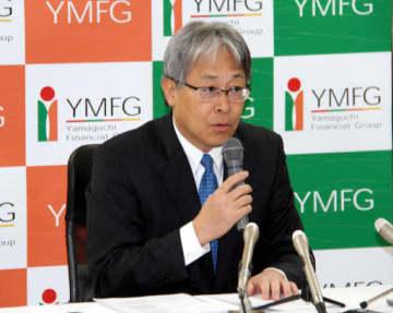 記者会見で愛媛銀行との業務提携を発表する山口FGの吉村社長