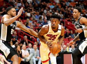 The Miami Heat's Jimmy Butler (22) squeezes between the San Antonio Spurs' Rudy Gay (22) and DeMar Rozan (10) in the second quarter at the AmericanAirlines Arena in Miami on Wednesday, Jan. 15, 2020. - CHARLES TRAINOR JR/Miami Herald/TNS