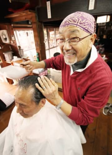 常連客と会話をしながら髪を切る瓜生薫さん=竹田市直入町上田北
