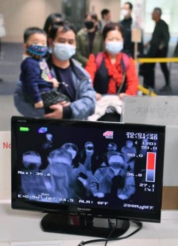 検疫検査場に設置されたサーモグラフィーの前を通過して入国する中国人観光客ら=22日午後4時半ごろ、那覇空港国際線ターミナル(落合綾子撮影)