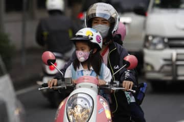 Masks have become another important protector besides crash helmets during rides along roads in Samut Prakan's Muang district, which has recorded very high ultra-fine dust PM2.5 levels. Wichan Charoenkiatpakul