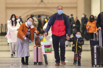 Travelers wearing face masks walk with their luggage at Hankou Railway Station in Wuhan in southern China's Hubei province.