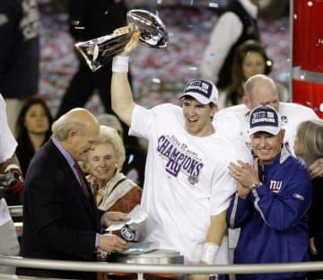 2008年2月、スーパーボウルを制覇し、優勝トロフィーを掲げるジャイアンツのQBイーライ・マニング(中央)=米アリゾナ州グレンデール(AP=共同)