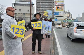 「123」の数字を記したプラカードを掲げる参加者=23日午前8時10分、徳島市のかちどき橋