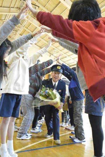 花道をくぐりながら笑顔を見せる田中さん=市立剣崎小学校