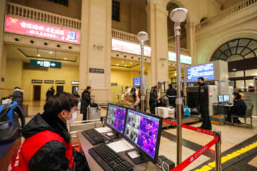 Staff members wearing masks monitor thermal scanners that detect temperatures of passengers at the security check inside the Hankou Railway Station in Wuhan, Hubei province, on Wednesday. (Reuters photo)