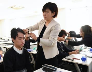髪形を整えて印象の違いを確認する学生(左)たち=22日、東大阪市の近畿大東大阪キャンパス