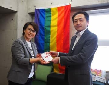 住友生命大阪広報センターの大野勝センター長(右)から寄付金を手渡される村木代表
