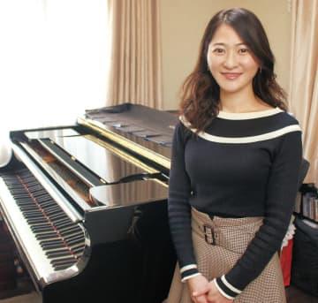 ピアノを前にほほ笑む西本さん
