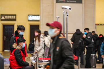 Staff members wearing masks monitor thermal scanners that detect temperatures of passengers at Hankou railway station in Wuhan, Hubei province, on Tuesday. (Reutes photo)