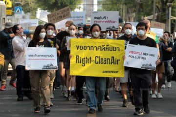 Activists march from Wat Benjamabophit to Government House on Thursday morning to call on the government to be serious about tacklikng the dust problem. (Photo by Chanat Katanyu)