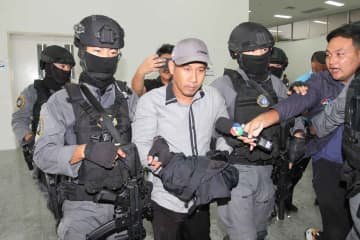 Armed police escort Prasittichai Khaokaew, who admits shooting and killing people during a gold shop robbery on Jan 9, at the Crime Suppression Division in Bangkok on Thursday. (Police photo)
