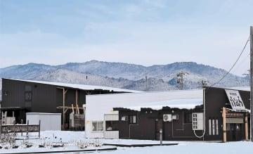 山形大xEV飯豊研究センター近くの田園地帯に立地するホテル(左)と屋台村