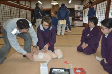 消防隊員(左端)から心肺蘇生法を学ぶ室生寺の職員ら=23日、奈良県宇陀市