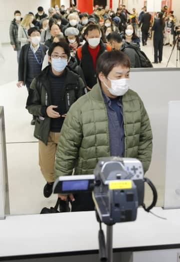 中国・武漢から成田空港に到着し、検疫を通過する乗客ら。手前は体温を測定するサーモグラフィー=23日午後