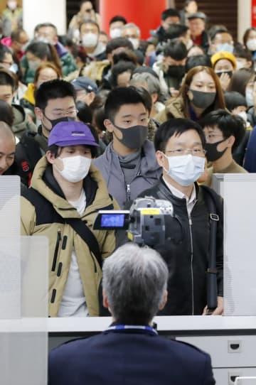 中国・武漢から成田空港に到着し、検疫を通過する乗客ら。手前は体温をサーモグラフィーで測定する検疫官=23日午後