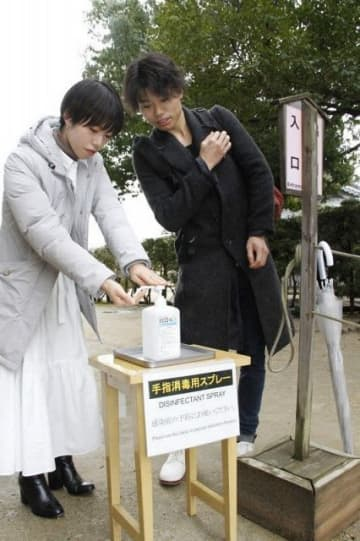 後楽園の正門脇から前に移された消毒液で手を洗う観光客