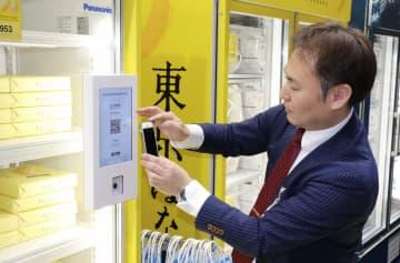 無人の陳列棚のパネルを操作するパナソニックの担当者=23日午後、関西空港