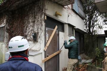 ドアに打ち付けてあった木材を外し、解体・撤去作業を始める業者=23日、厚木市