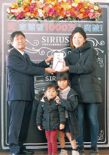 大木市長(左)から1000万人目の記念品を受け取る早稲塚永華さん、華ちゃん、桃ちゃん(右から)