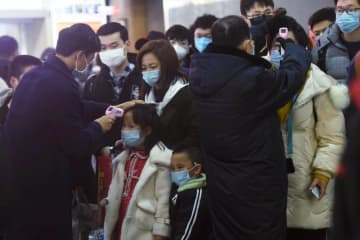 Staff members check body temperatures of the passengers arriving from the train from Wuhan to Hangzhou in Zhejiang province at Hangzhou Railway Station ahead of the Chinese Lunar New Year on Thursday. (Reuters photo)