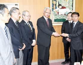 善意を手渡す山地代表取締役(右端)