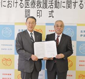 協定書を手に笑顔を見せる菊谷市長(右)と上田支部長