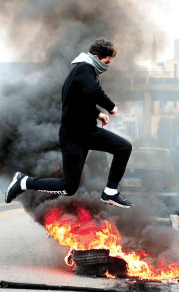 A Lebanese protester jumps over a roadblock near the Camille Chamoun Sports City Stadium in Beirut on Thursday.