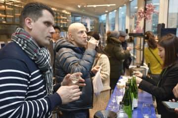福島県の酒と食材を紹介する展示会で試飲する来場者=23日、パリ日本文化会館(共同)