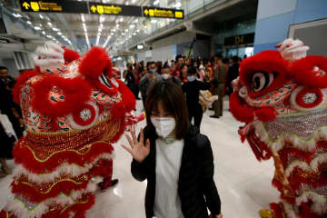 A Chinese tourist wears a mask as she arrives at Suvarnabhumi airport on Wednesday, ahead of the  Lunar New Year celebration  in Bangkok. (Photo: Reuters)