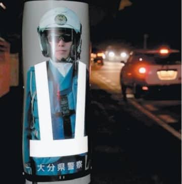 市道沿いの電柱に張られた白バイ隊員の等身大カラー写真=23日夜、大分市明野東