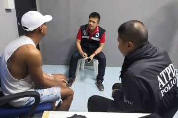 Phakphum, left, is questioned by police at a resort in Nakhon Ratchasima's Sikhiu district for allegedly pimping five schoolboys to male customers. All the boys were rescued. (Photo by Prasit Tangprasert)
