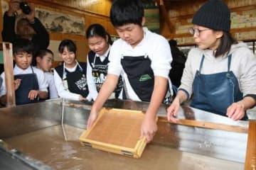 神代和紙保存会のメンバー(右)から教わりながら紙すきをする児童たち