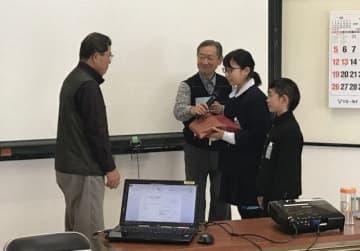 細川会長(左)に手紙を預ける平島小児童