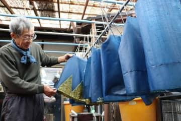 巨椋池干拓田のタデアイを使った藍染めで染め上げた麻布。だんだら模様や「誠」の文字は、もち米ののりで防染している(京都市伏見区・染司よしおか)