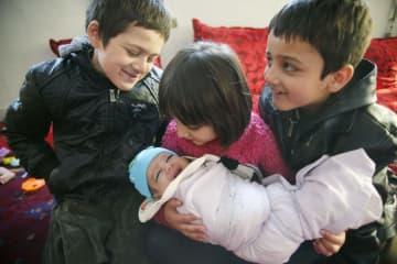 アフガニスタンの首都カブールで、ナカムラ・ムスリムヤールちゃん(中央下)に「笑って」と話し掛けるきょうだいら=22日(共同)