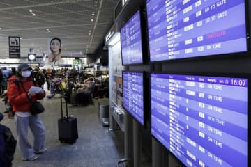 A passenger looks at a flight information board displaying a cancelled flight to Wuhan in a departure hall at Narita Airport near Tokyo on Thursday. (Bloomberg photo)