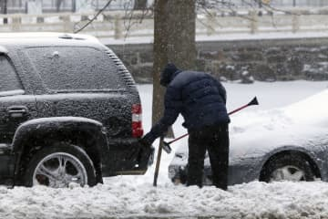 Man cleans car with brush during snow storm in New York. - Dreamstime/Dreamstime/TNS