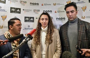 24日、ドイツ西部リューネンでの記者会見で話すキミア・アリザデ選手(中央)(AP=共同)