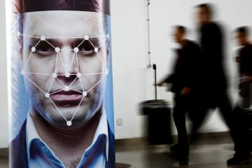 People walk past a poster simulating facial recognition software at the Security China 2018 exhibition on public safety and security in Beijing.