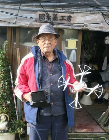 自宅の工房前でドローンを手ににこやかな表情の岡本さん(南丹市美山町豊郷)