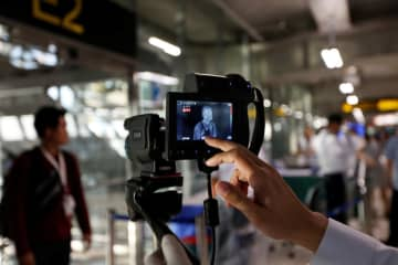 An official uses a thermal camera at the arrivals hall of Suvarnabhumi airport on Friday as a measure to prevent the spread of coronavirus in Bangkok. (Reuters photo)